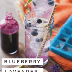 Blueberry Lavender Cocktail on an orange linen with a bottle of blueberry syrup and a blue ice cube tray