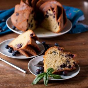Basil blueberry bundt cake with two slices cut out on separate plates in the foreground with fresh blueberries scattered around