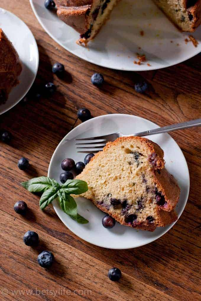 close up of a slice of basil and blueberry bundt cake on a white plate with a silver fork. Fresh blueberries scattered around
