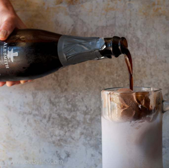 Stout beer being poured into a frosty mug filled with chocolate ice cream