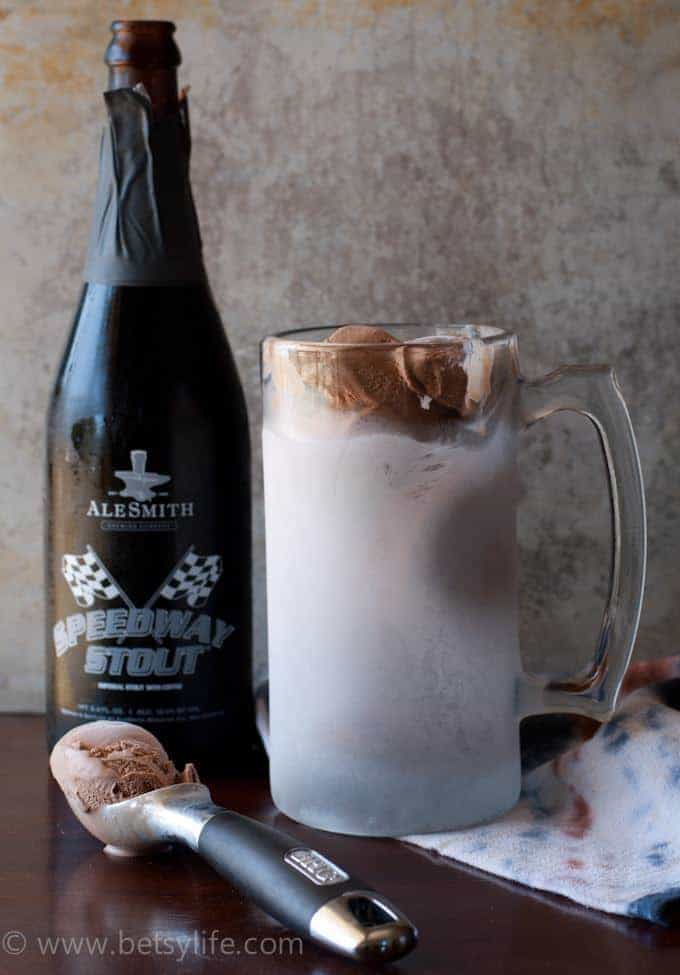 frosted mug filled with chocolate ice cream next to a bottle of stout beer