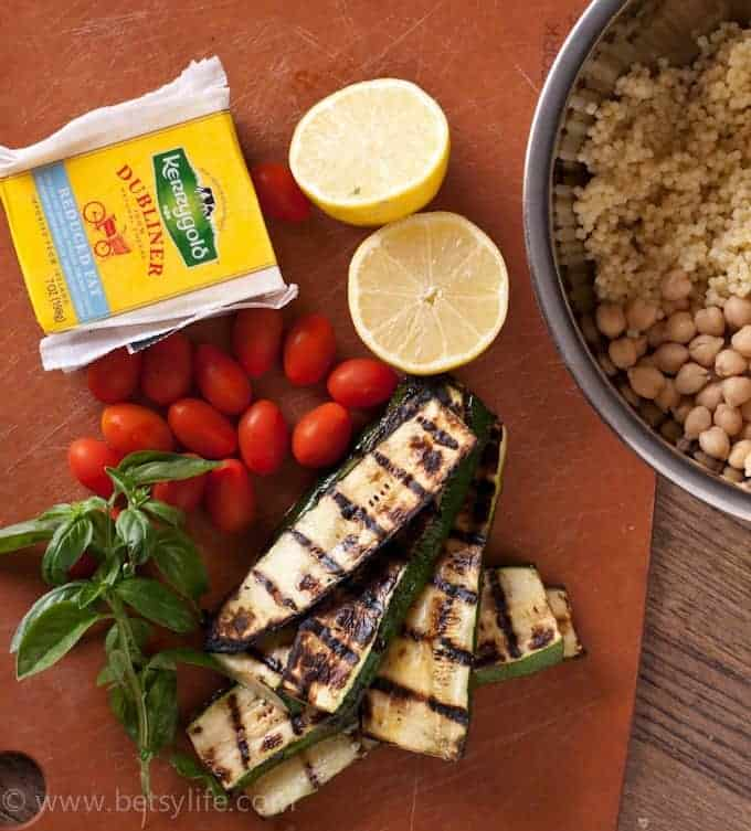 overhead photo of summer pasta salad ingredients. Dubliner cheese, grilled zucchini, lemon, tomatoes, basil, quinoa and chickpeas