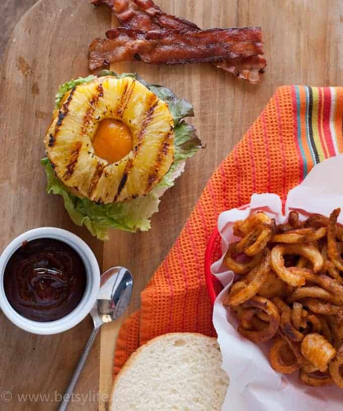 Overhead assembly of bbq bacon hawaiian burger next to strips of bacon, curly fried and a dish of bbq sauce