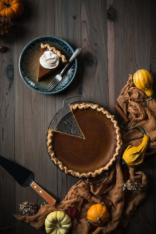 Overhead of pumpkin pie with one slice removed. Slice on a blue plate and topped with whipped cream. Natural fabric around the edge with gourds.