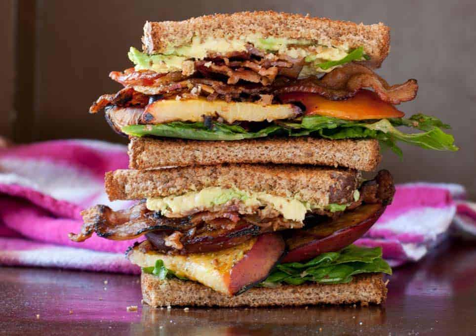 Bacon, Lettuce, and Grilled Peach Sandwich sliced in half and stacked. Tie dye linen out of focus in the background