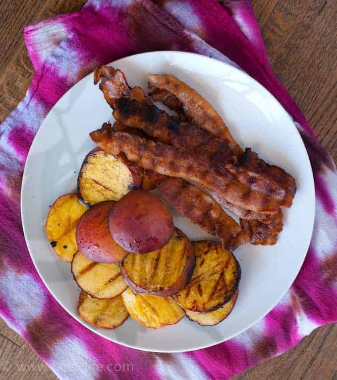 grilled bacon and sliced peaches on a white plate sitting on top of a fuschia and white tie-dyed linen