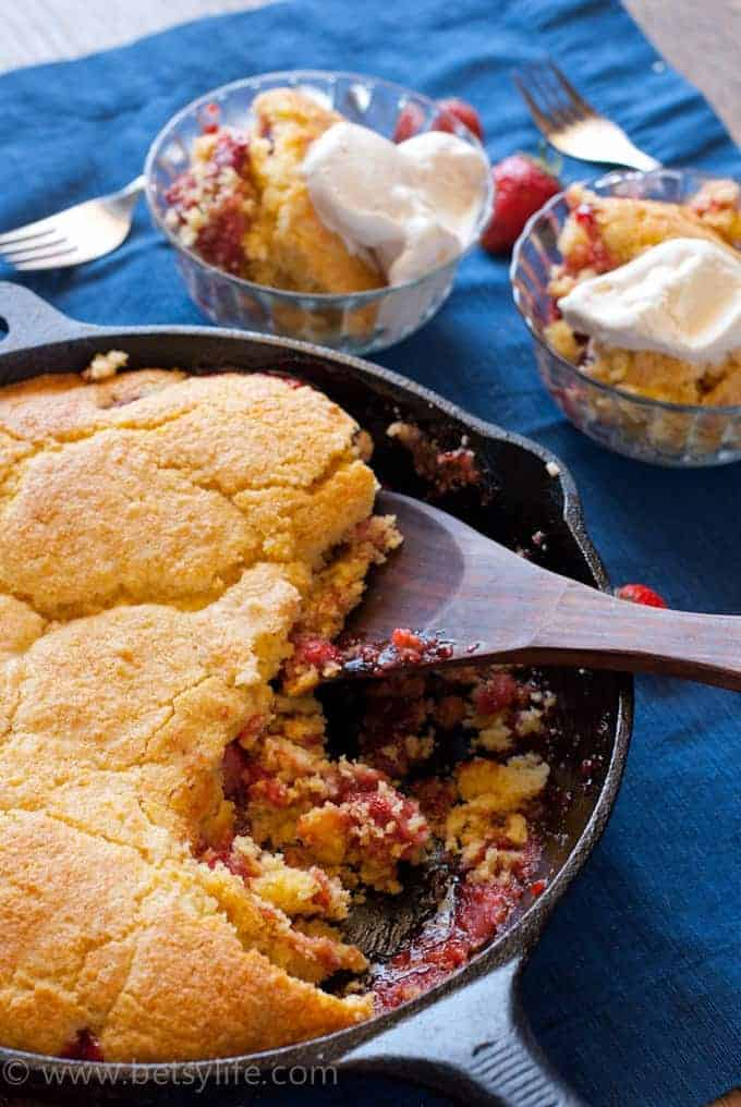 Dark blue background with a cast iron skillet filled with strawberry cobbler with cornbread topping. Wooden spoon in the cobbler and two servings are spooned out into glass bowls out of focus in the background