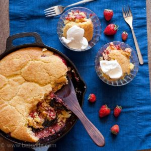 Dark blue background with a cast iron skillet filled with strawberry cobbler with cornbread topping. Wooden spoon in the cobbler and two servings are spooned out into glass bowls on the side. Two forks and 7 whole strawberries scattered around.