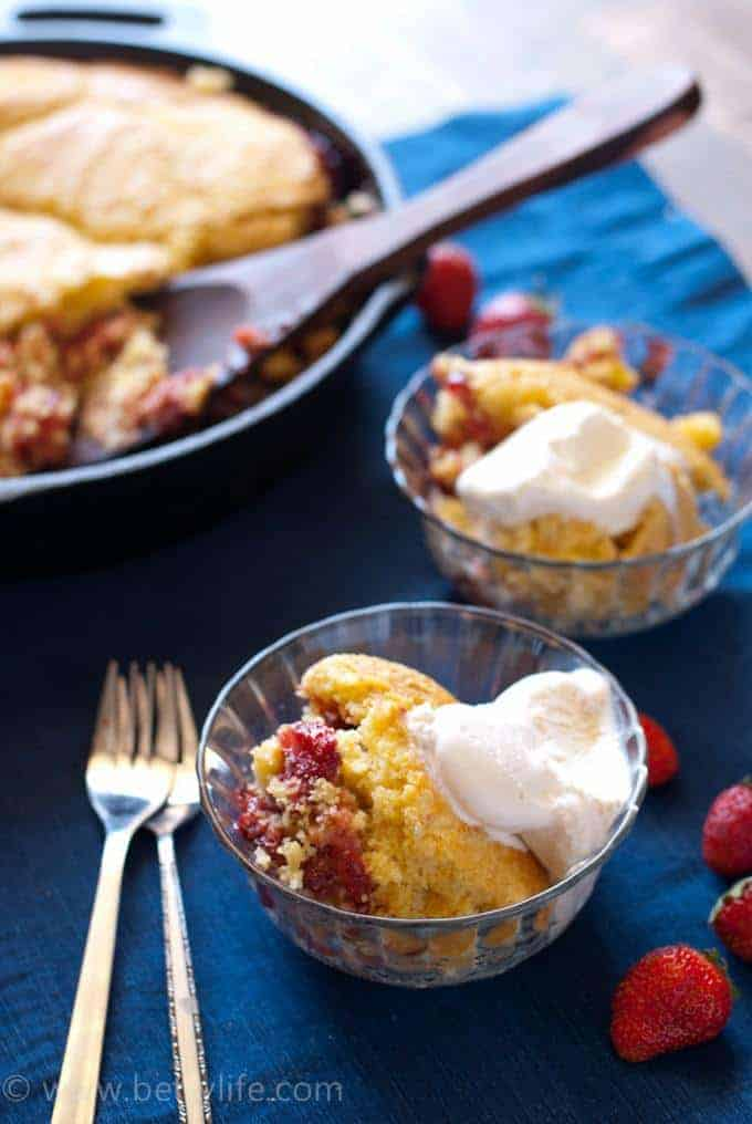 Dark blue background with a cast iron skillet filled with strawberry cobbler with cornbread topping out of focus in the background. Wooden spoon in the cobbler and two servings are spooned out into glass bowls in the foreground with two forks and 7 whole strawberries scattered around.
