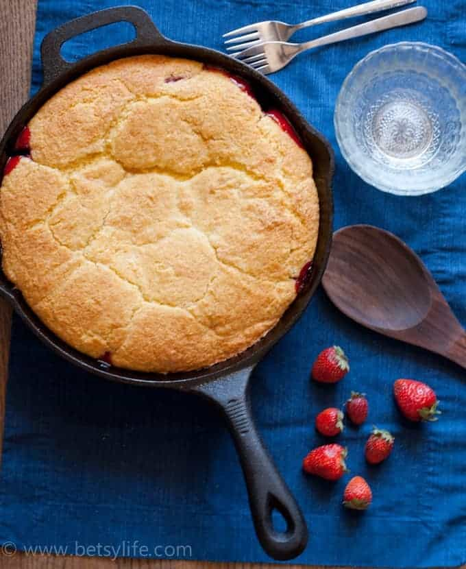 Dark blue background with a cast iron skillet filled with strawberry cobbler with cornbread topping. Clear glass bowls, whole strawberries, forks and a wooden spoon on the side