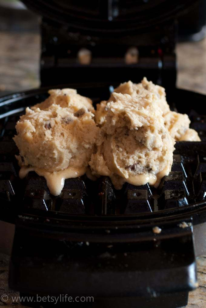scoops of raw cookie dough inside a waffle iron