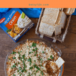 Round baking dish of cheesy tater tot bacon dip next to crackers and onion soup mix