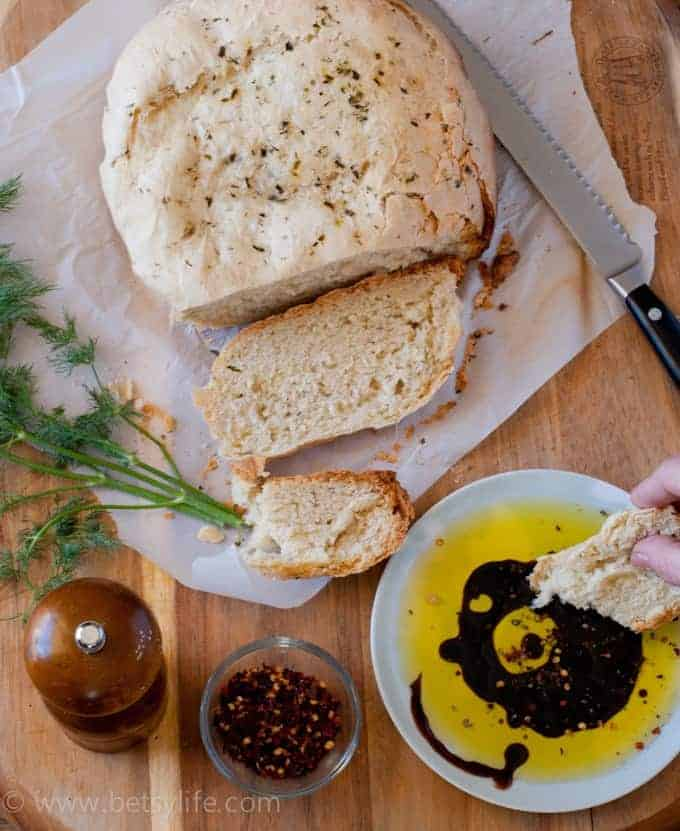 sliced bread loaf. hand dipping bread into olive oil