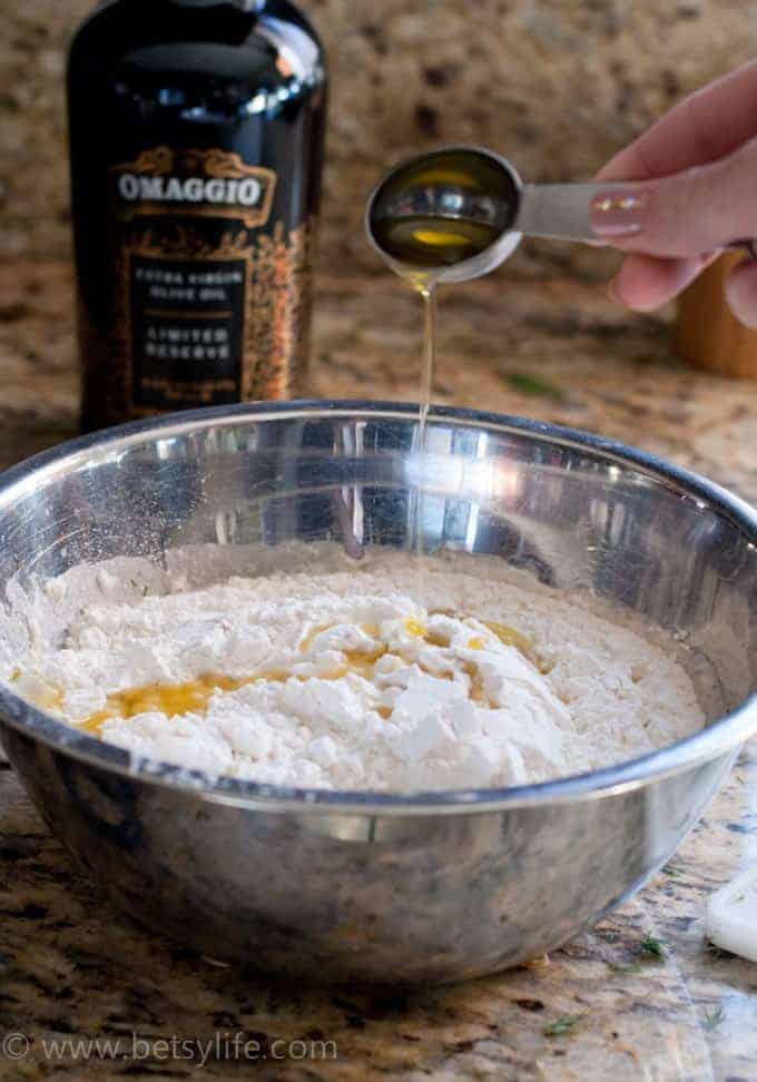 olive oil drizzling into a bowl of flour