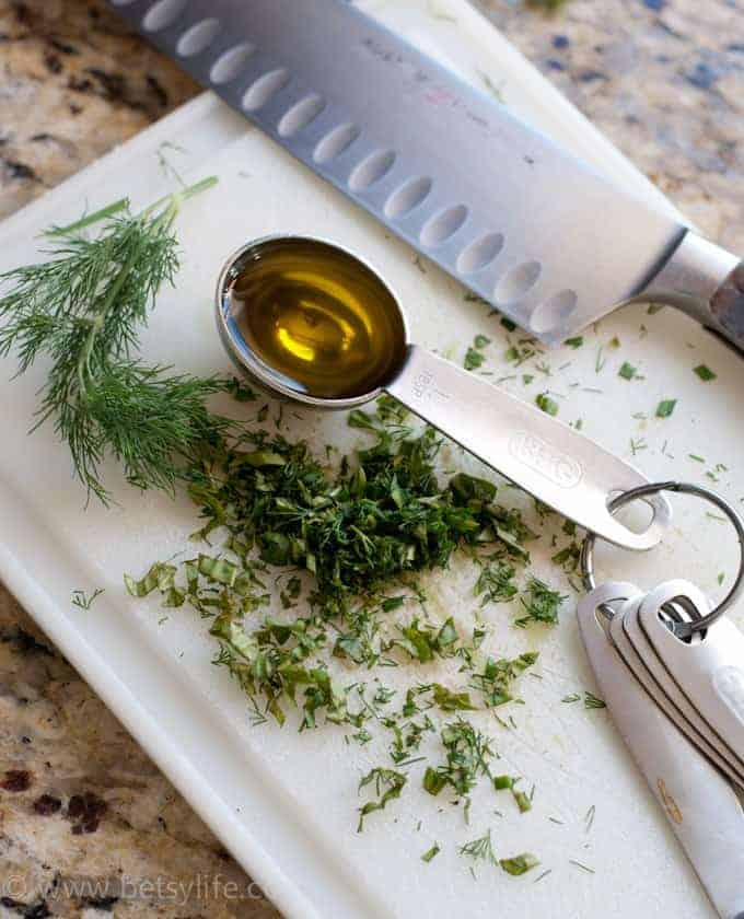 tablespoon filled with olive oil on a cutting board with fresh chopped herbs
