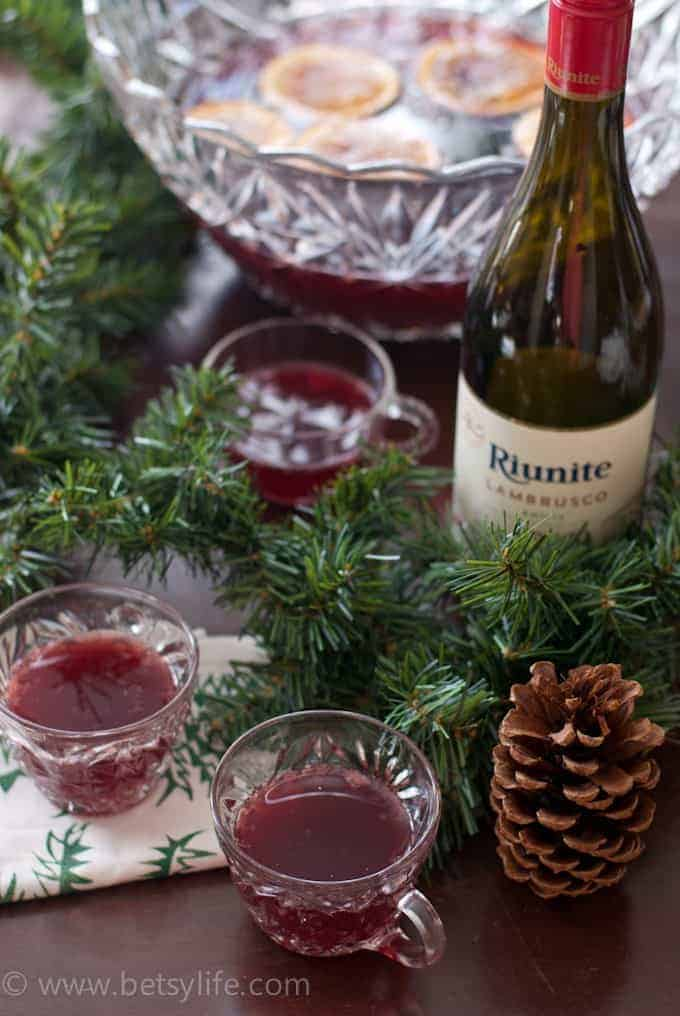 Three punch glasses of Red Wine Holiday Punch surrounded by pine garland