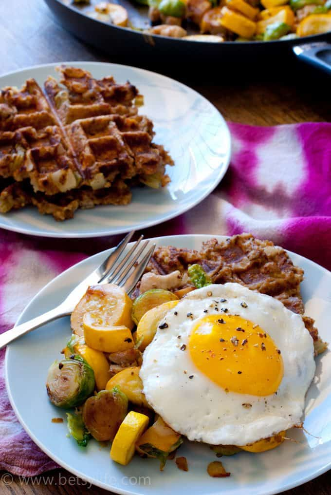 plate with waffles, fried egg, and vegetables