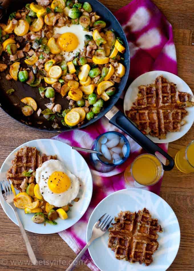 Overhead view of thanksgiving leftovers brunch. Leftover stuffing waffles on three plates and leftover turkey and vegetable hash in a skillet on a tie dye dish towel