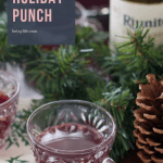 Punch glass of Red Wine Holiday Punch surrounded by pine garland