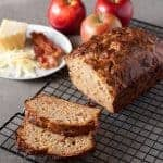 Bacon Apple Cheddar Bread loaf sliced on a cooling rack with apples in the background