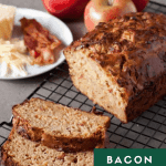 bacon apple cheddar bread sliced on a cooling rack with apples in the background