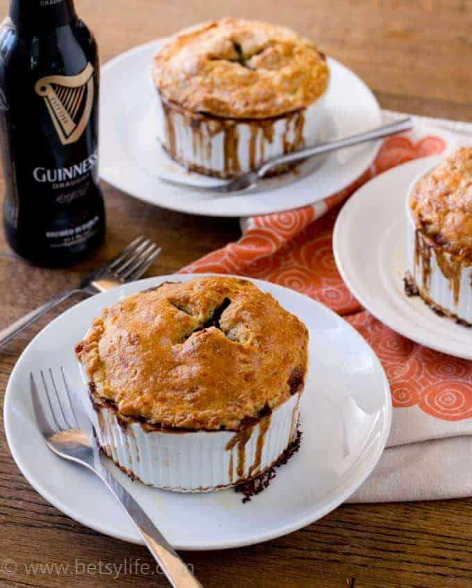 Three individual pot pies on plates with forks and a Guinness beer in a bottle