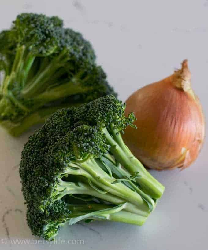 2 heads of broccoli and a yellow onion in the skin on a white counter