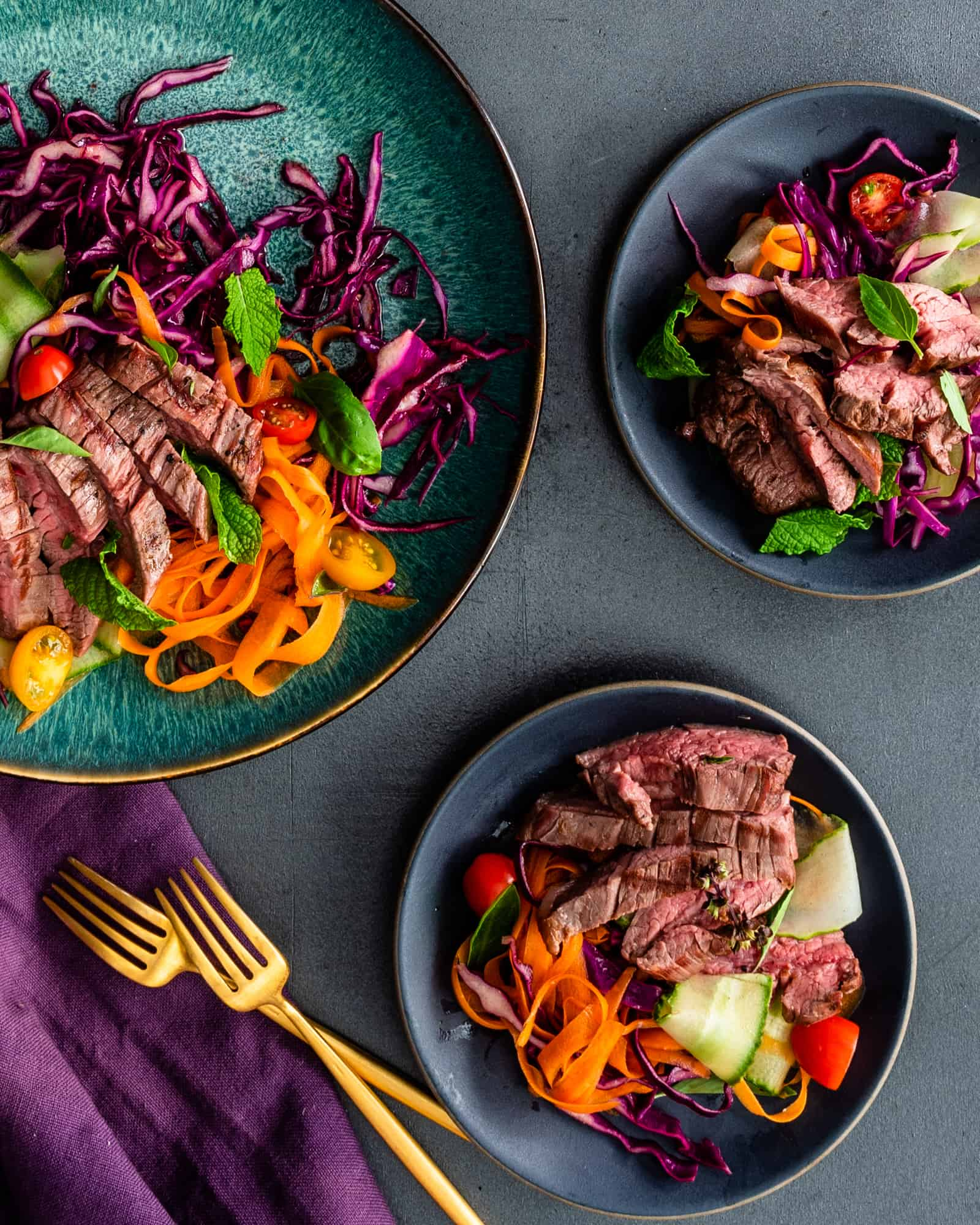 three plates of Thai steak and noodle salad with gold forks on a dark background