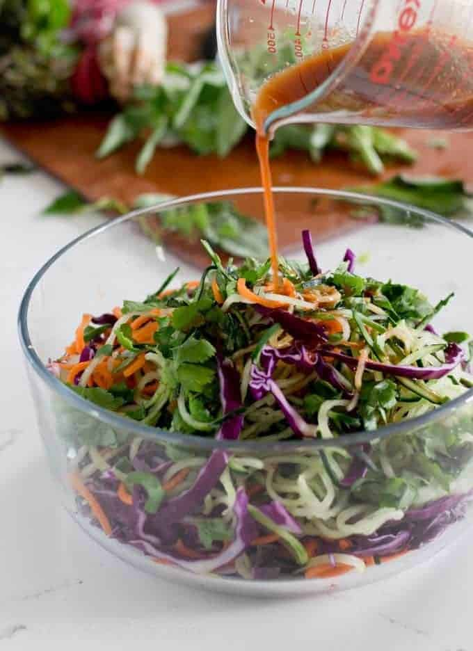 dressing pouring over a colorful salad in a glass bowl