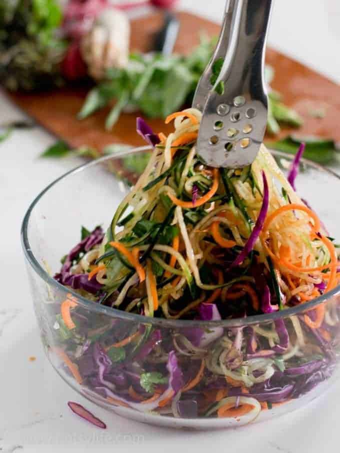 Tongs tossing a spiralized vegetable salad