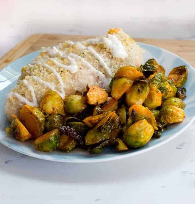 Buffalo Brussels Sprouts on a plate with a breaded chicken breast