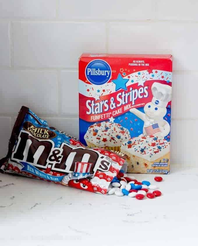 bag of red, white and blue m&ms on a counter spilling out next to a box of pillsbury stars and stripes cake mix
