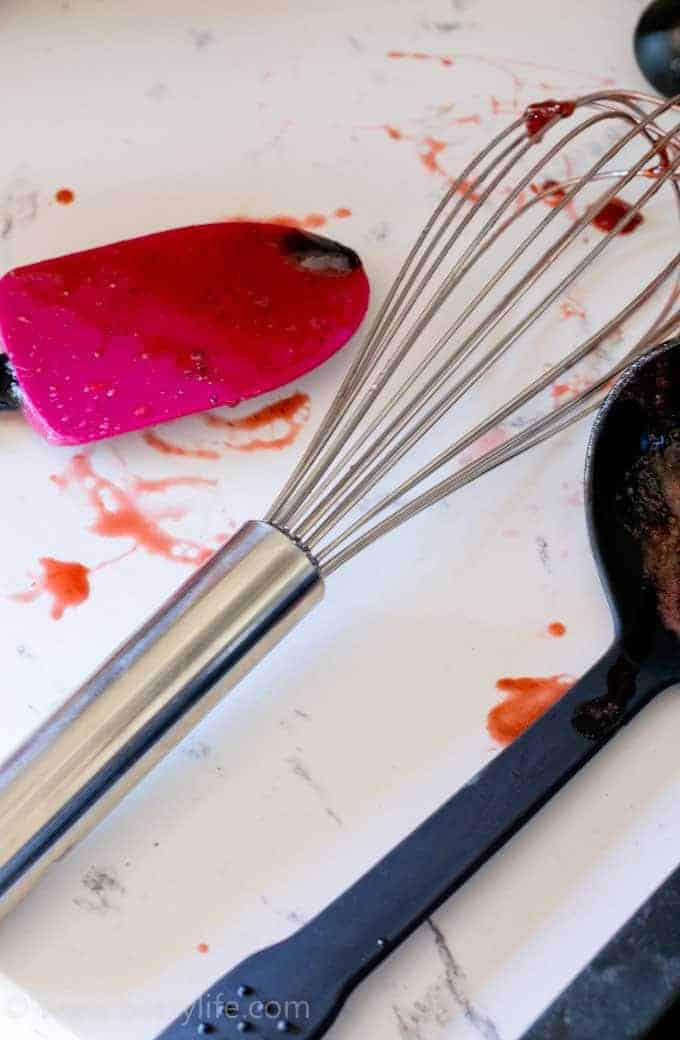 white counter with dirty spatula, whisk and ladle covered in homemade strawberry jam
