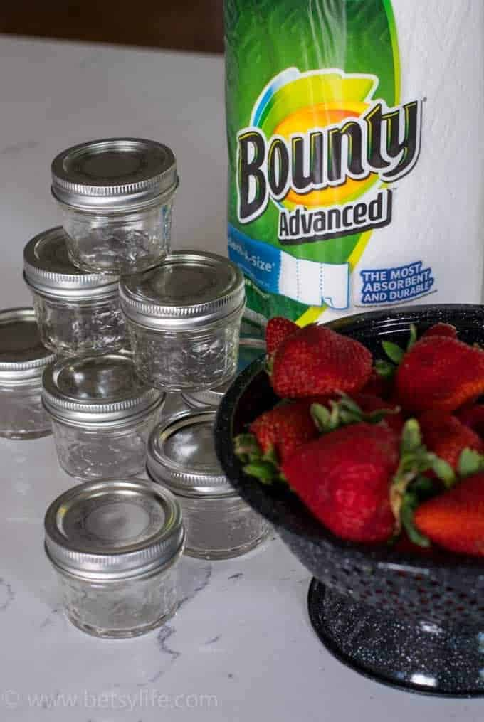 homemade strawberry jam prep. Empty jars, roll of paper towels. colander full of fresh washed strawberries