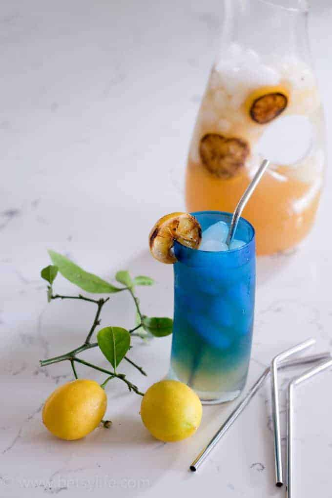 best lemonade recipe in a blue glass with a grilled lemon slice on the edge of the glass. clear pitcher out of focus in the background. Two lemons and 3 metal straws scattered around in front