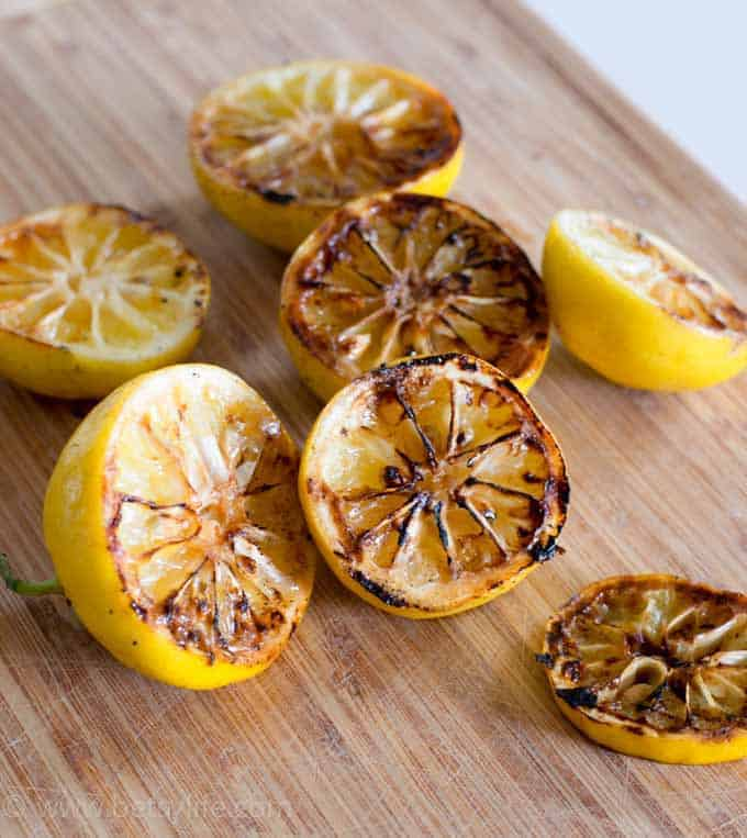 Grilled lemon halves on a cutting board