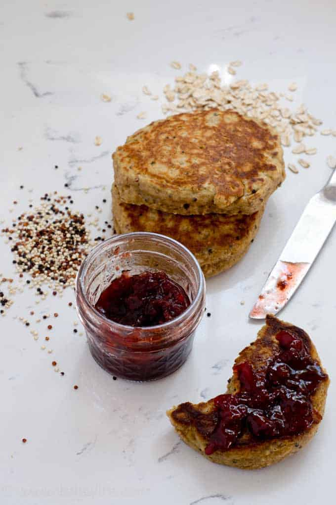 three healthy pancakes next to a jar of jam and scattered oats and quinoa. One pancake has jam spread on it.