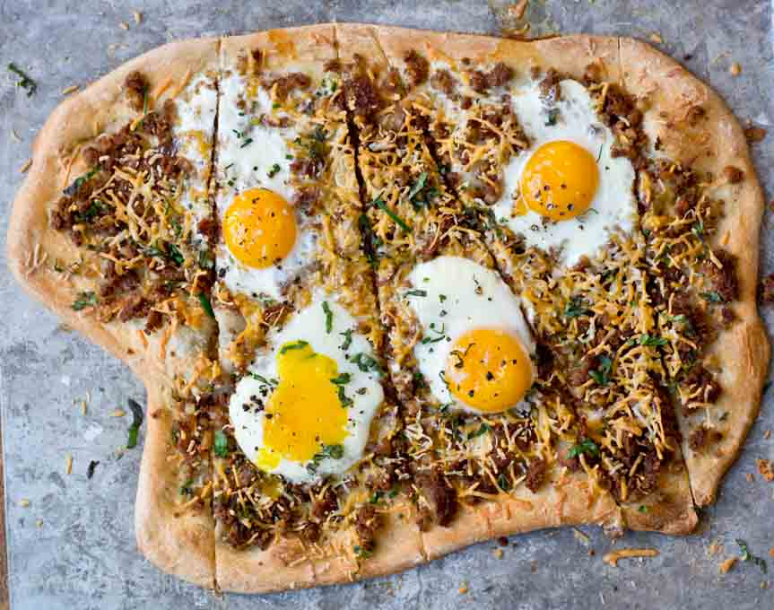 Corned Beef Hash pizza topped with eggs and sliced