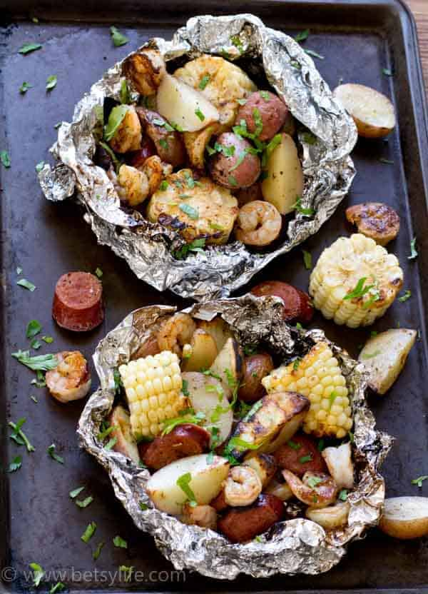Two Low Country Boil Foil Grill Packets on a sheet pan