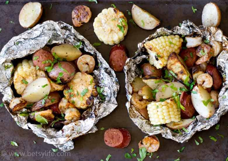 Two low country boil grill packets with ingredients around the sides