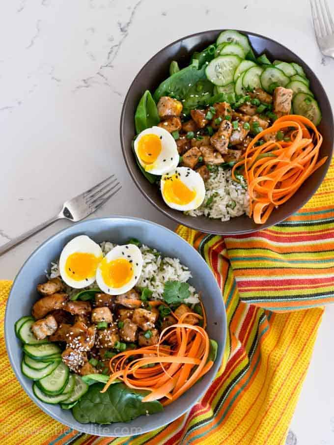 Healthy 30 minute meal. Two pork and rice bowls on a yellow striped linen. Pork, carrot ribbons, thinly sliced cucumber, and runny yolk eggs
