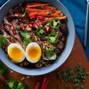 blue bowl of meat and vegetables with soft-cooked egg