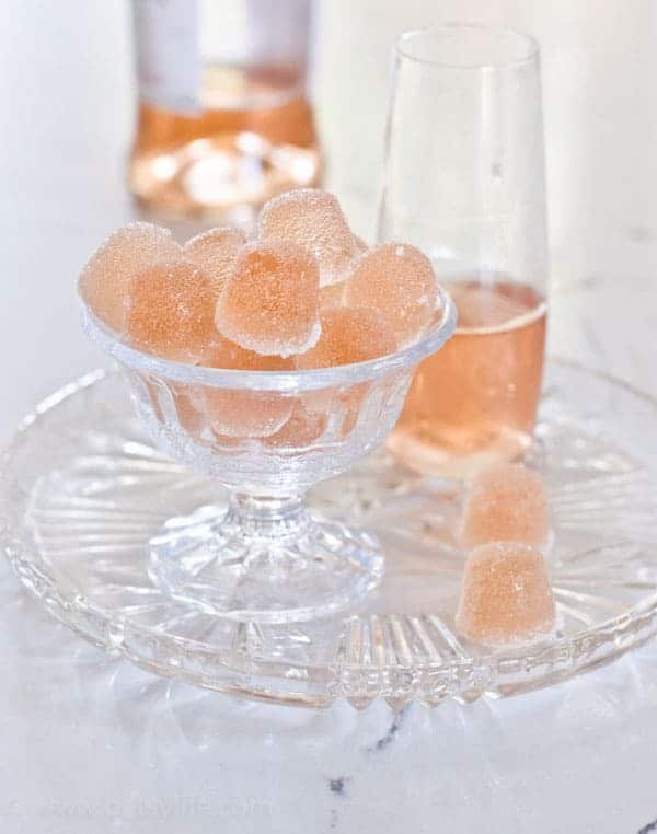 Sugared Rosé Wine Gummies in a glass dish next to a glass of pink wine