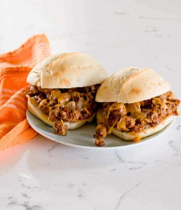 two Individual oven Baked Sloppy Joes on a plate next to an orange napkin