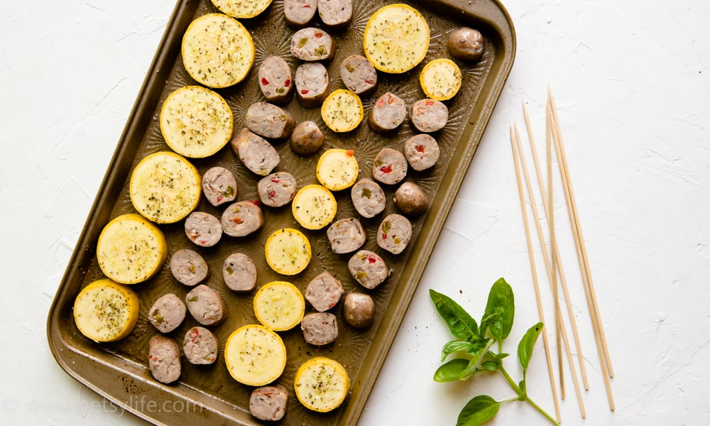 Slices of sausage and summer squash on a sheet pan next to wooden skewers