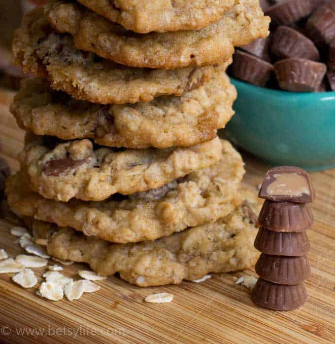 Close up of Salted Peanut Butter Cup Cookies next to a stack of mini peanut butter cups. Top cup is cut in half to show the inside