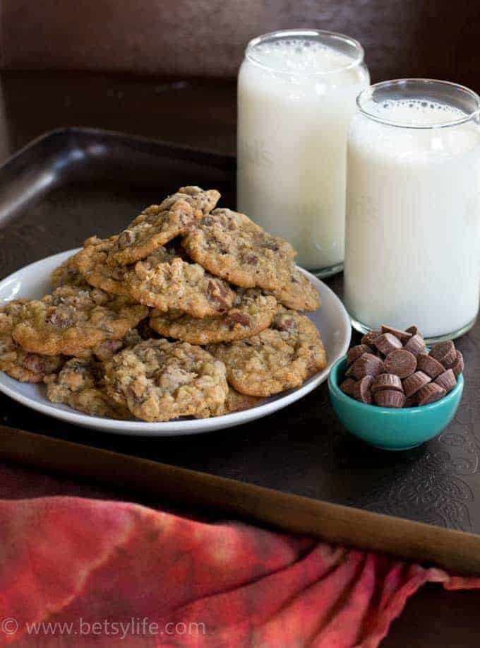 Salted Peanut Butter Cup Cookies heaped on a white plate with a teal bowl filled with mini peanut butter cups and two glasses of milk on the side