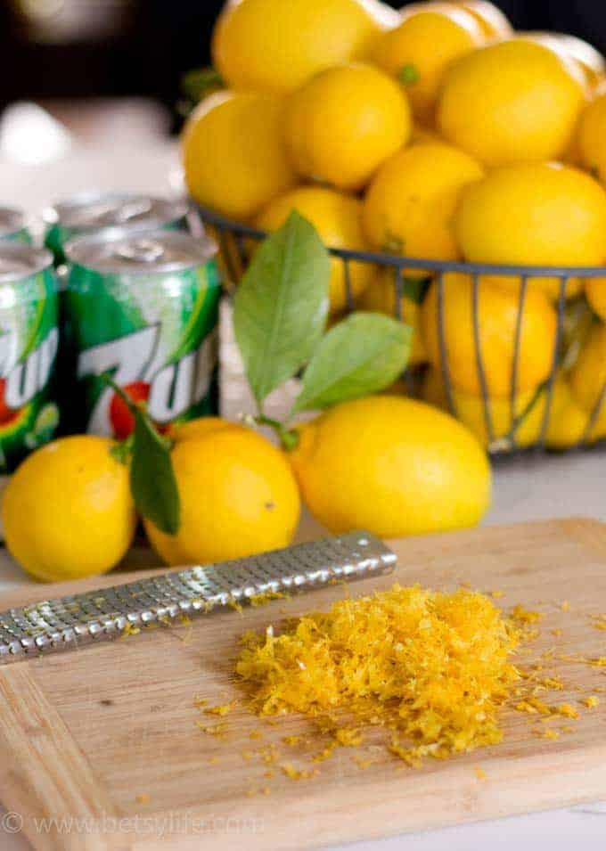 pile of lemon zest next to a basket of lemons and a can of 7up