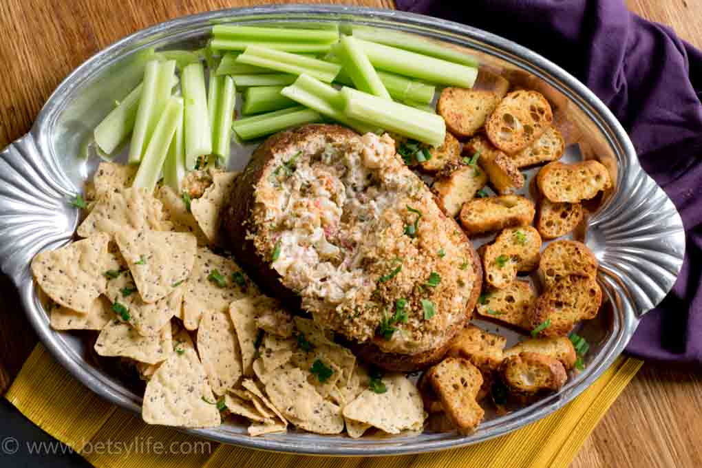 Spicy Baked Shrimp Dip on a silver platter with tortilla chips, celery sticks, and crostini