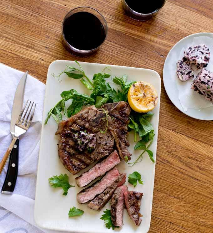 Grilled T-Bone with Red Wine Compound Butter on a rectangle plate surround by fresh herbs and a grilled lemon half